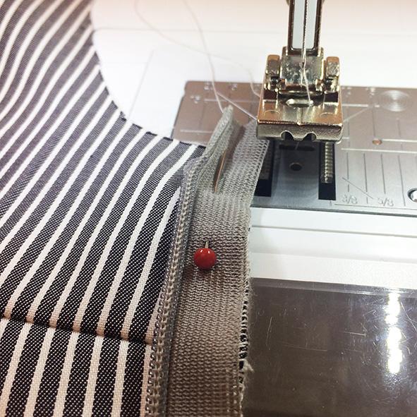 Der Nahtreißverschluss liegt auf der Nähmaschine und ist festgenagelt an die Nahtzugabe