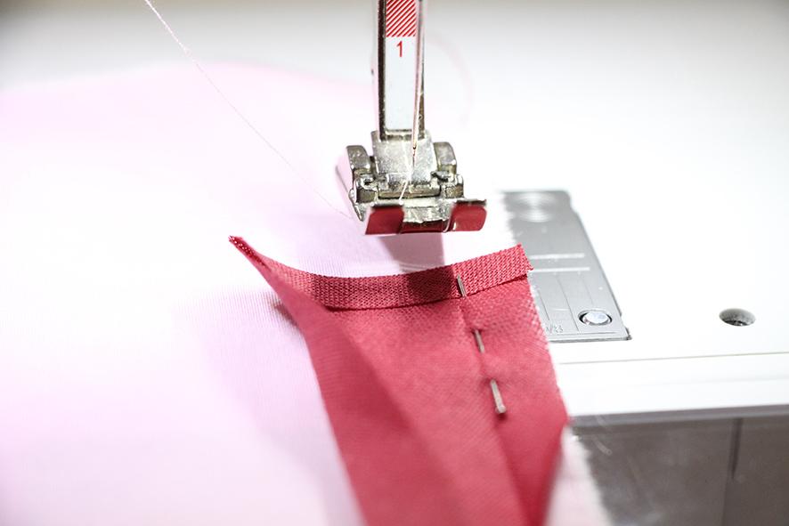 Das Schrägband ist bereit zum annähen mit einer Stecknadel befestigt. Die Kante nach innen geklappt.