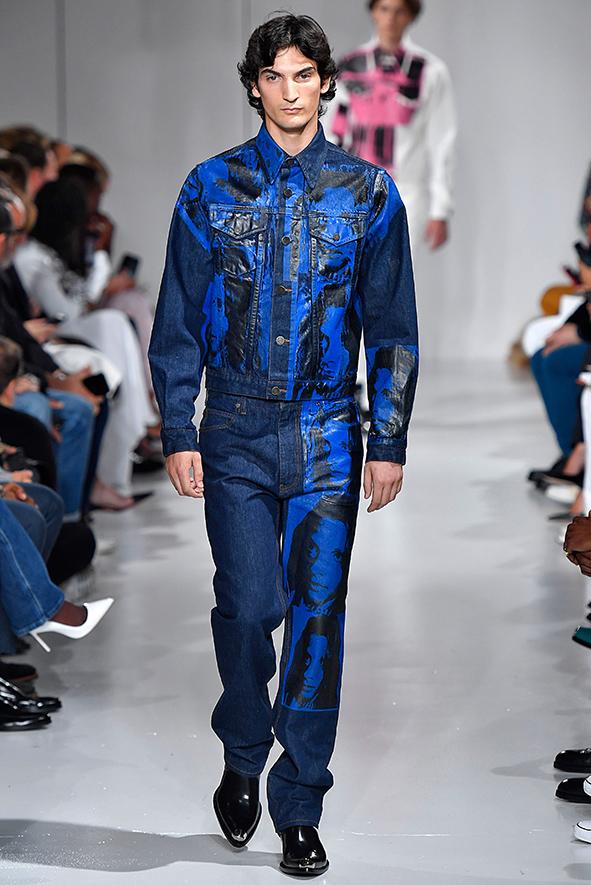 Calvin Klein Männermodel präsentiert einen Zweiteiler aus klassischem Denim und bedruckten Lederpatches.