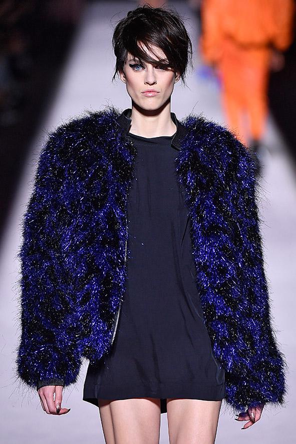 Laufsteg-Look von Tom Ford aus der Frühjahr-/Sommerkollektion 2018. Glamouröser Sixties-Look mit kurzer Felljacke, getragen auf einem lässigen schwarzen Kleid.