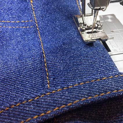 Der Bund einer Jeans wird abgesteppt.