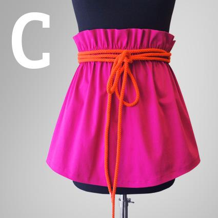 Ein linker Rock mit neon oranger Kordel ist auf eine Büste gezogen.