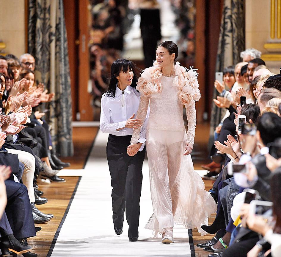 Gezeigt wird die Designerin Bouchra Jarrar auf der Fashionweek Paris 2017, begleitet von einem Model, die ein Kleid der aktuellen Kollektion trägt.