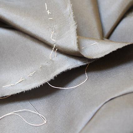 Der Faden ist durch beide Stofflagen genäht und zwischen den Stofflagen aufgeschnitten worden.