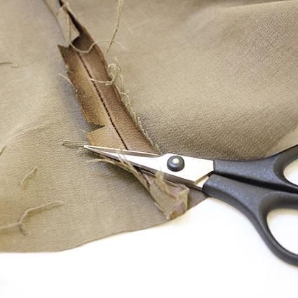 Eine Stickschere liegt auf der eingeschnittenen Nahtzugabe.