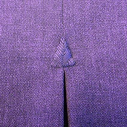 Eine handgestickte Fliege in Form eines Dreieckes ist am Anfang einer Falte abgebildet.