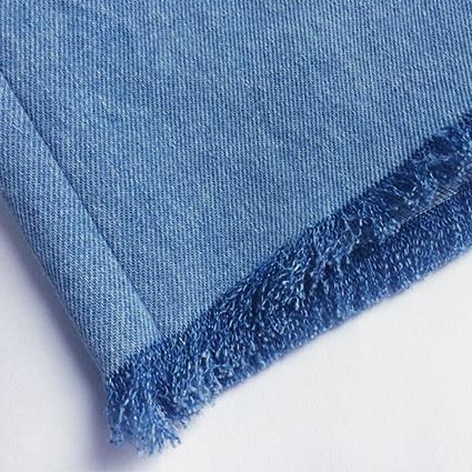 Ein ausgefranster Saum eines Jeanskleides ist zu sehen.