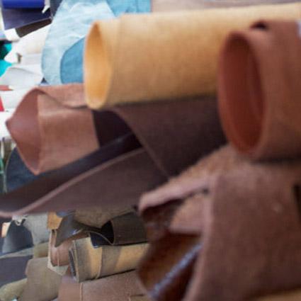 Verschiedene Lederarten sind in einem Regal zu sehen.