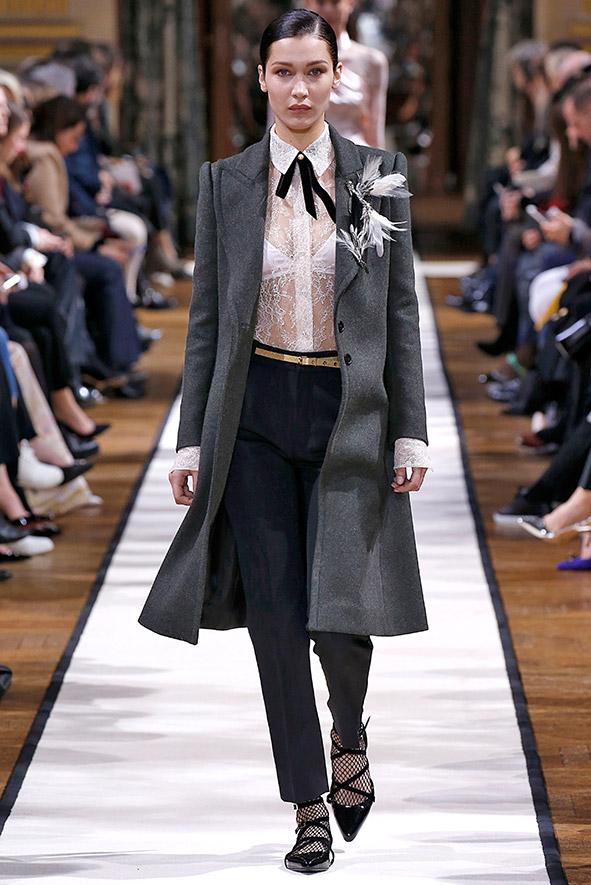 Lanvin zeigt auf der Fashionweek in Paris in seiner Herbst-/Winterkollektion eine transparente, hochgeschlossene Spitzenbluse mit Schleife kombiniert mit einem grauen Mantel und einer schwarzen Anzugshose.
