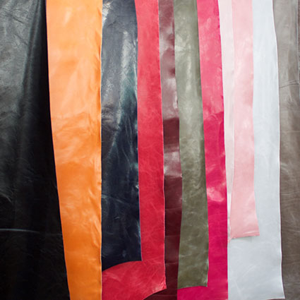 Verschieden farbiges Leder hängt übereinander gelappt auf einer Stange.