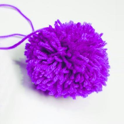 Ein lilafarbener Pompom aus Wolle ist zu sehen.