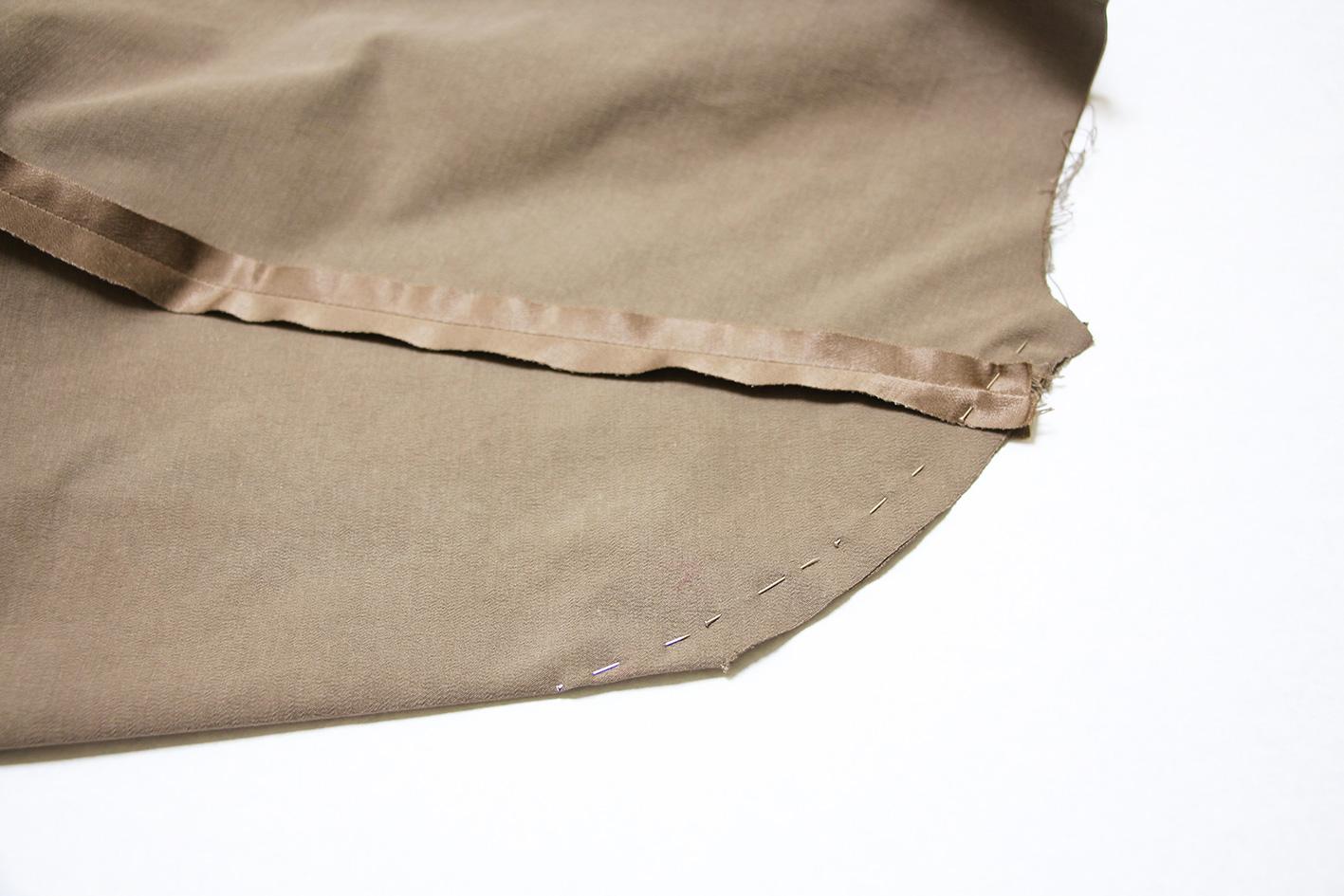 Ein Stoff mit einem Abnäher liegt flach auf und ist mit Stecknadeln befestigt.
