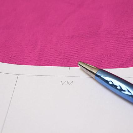 .Das Schnittteil mit der Knipsmarkierung an der vorderen Mitte liegt auf dem Stoff.
