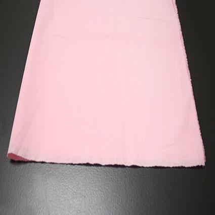 Rosa farbender Stoff liegt auf dem Tisch in seiner vollen Stoffbreite.